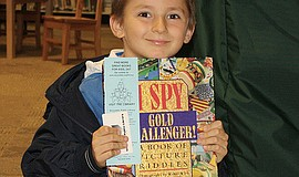 A child with a book at the Escondido Public Library.