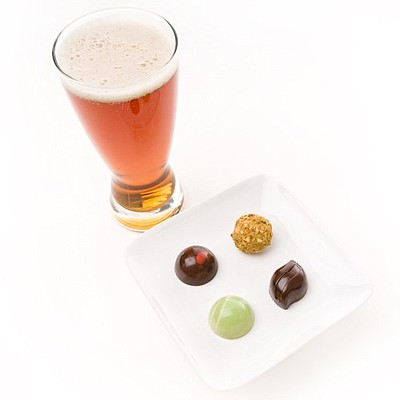 Photo of a glass of beer and a small plate of chocolate.