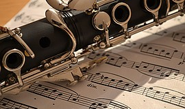 A file photo of a clarinet resting on a sheet of music.