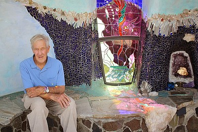 James Hubbell sits next to his artwork.