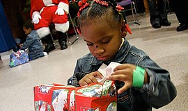 Photo of a little girl opening a present provided by a past toy drive. Courte...
