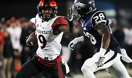 Running back Donnel Pumphrey stiff arms Nevada Wolf Pack corner back Elijah M...