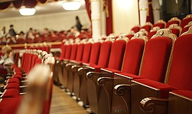 A stock photo of red theater seats.