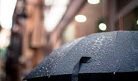 A stock photo of an umbrella in the rain.