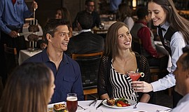 Promotional photo of guests at Fogo de Chão Brazilian Steakhouse.