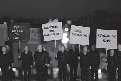 3D-printed figurines of the artist carrying protest signs...