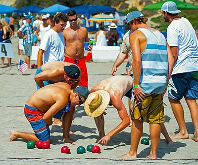 Promotional photo of people playing bocce on the beach. C...