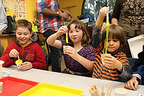 Promotional photo of three kids crafting for Fleet Scienc...