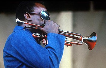 Promotional photo of musician Miles Davis playing the tru...