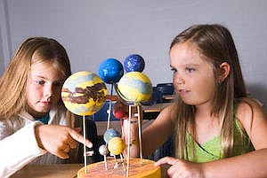 Promotional photo of girls looking at space models. Court...