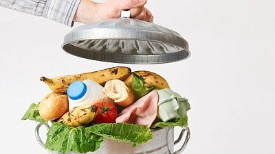 Promotional graphic of food tossed into a garbage can. Co...