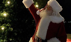 Promotional photo of Santa Claus in front of a christmas ...