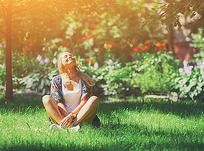 Promotional photo of a woman sitting in the grass. Courte...