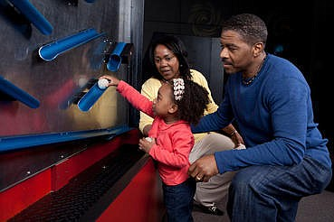 Promotional photo of a family at Design Zone exhibit. Cou...