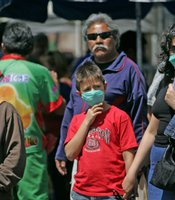 Pedestrians wear surgical masks along Constitution Avenue April 25, 2009 in Tijuana, Mexico. Sandy Huffaker/Getty Images.