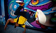 Jeremy Mascardo breakdancing in front of Mr. Maxx Moses' (AKA Pose2) street mural on the wall outside the Art Academy of San Diego.