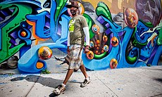 San Diego Southern California Mural Artist, Mr. Maxx Moses (AKA Pose2) in Barrio Logan (Chicano Park) walking in front street art mural by Crol vs Werc & Pose2.