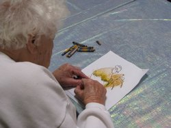 A client with Alzheimer's disease works on her coloring at Casa Pacifica Adul...