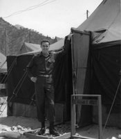 "U.S. Army Signal Corps Second Lieutenant William Orcutt standing in front of his bunk during the Korean War.  Caption written by William Orcutt (to his wife Beverly) ""An un-light-steady view of your husband in his battalion abode"""