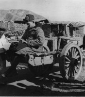 American GI sitting on the back of a mule-drawn buggy typing on a typewriter with elderly Korean man looking on.  Photo taken during the Korean War.