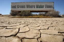 A sign on a farm trailer reading 'Food grows where water flows,' hangs over d...