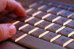 A hand rests on the keys of a laptop keyboard.