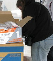 Exchange workers check on their supply of syringes.