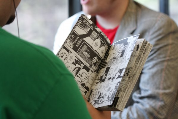 Passenger reading comics on trolley headed toward Comic-Con.