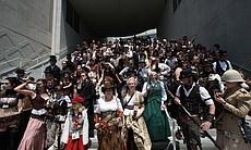 Hundreds of people dressed in steampunk garb gather on the stairs of the convention center.