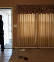 LONGMONT, CO - FEBRUARY 18: Boulder County sheriff's deputy Rick Ferguson tapes a 'no trespass order' on the front door of a home that was forclosed in Longmont, Colorado. The tenants had stopped paying their mortgage payments two months before and then moved out just prior to the eviction. (John Moore/Getty Images)