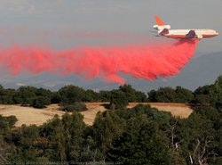 A McDonnell Douglas DC-10 drops flame retardant on a field. The state says it...