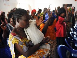 A Congolese rape victim joins others in raising their hands as they pray at a...