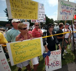 A large crowd protests President Obama's health care position outside of the high school where the President was conducting a town meeting on August 11, 2009 in Portsmouth, New Hampshire.