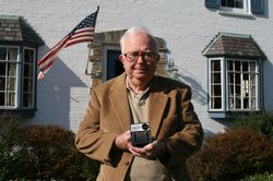 "Photo of ham radio enthusiast, Wayne Gilbert, who came across this hand-sized black box with the wording ""National Emergency Alarm Repeater, Civilian Warning Device."""