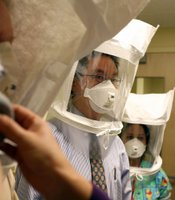 Karya Lustig sprays a chemical mist into a hood as she fits and trains doctors and nurses how to use the N95 respiratory mask at the La Clinica San Antonio Neighborhood Health Center April 28, 2009 in Oakland, California.