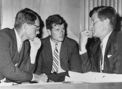 Attorney General Robert Kennedy (1925-1968), Sen. Edward Kennedy and President John F. Kennedy (1917-1963) talk while seated behind a desk in a 1962 photograph.