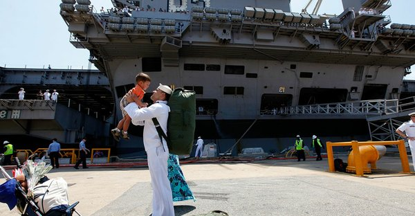 Sailor Eliezer Arroyo holds his 23 month old son Eliezer Jr. up in the air after stepping off of the USS Eisenhower after it arrived on July 30, 2009 in Norfolk, Virginia.