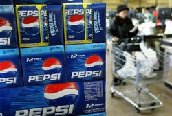 A shopper passes a display of 12-packs of Pepsi at a market in Des Plaines, I...