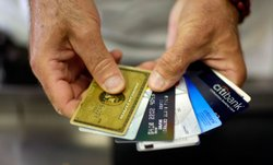 Alain Filiz shows off some of his credit cards as he pays for items at Lorenz...
