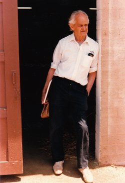 Manny Farber, academic, film critic, and artist, rests in the shade of a door...