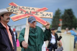 Brian Stern of Belgrade, Montana protests outside a town hall meeting on heal...