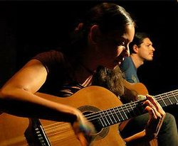 Gabriela pounds on the body of the guitar adding percussion to the duo classical guitar music.