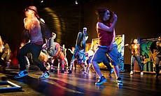 Hip-hop dancers perform fast-moving jumps, stomps and flips to the beat of the music.