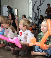Children watching Jason Hackenwerth make balloon animals at the New Children's Museum.