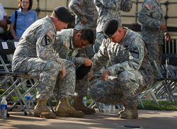 U.S. Army soldiers grieve together during the memorial service in honor of the thirteen victims of the shooting rampage allegedly by U.S. Army Major Nidal Malik Hasan on November 10, 2009 in Fort Hood, Texas.