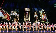 The show features dynamic performance routines within a signature production number set in Times Square, lighting up the New York skyline with a glittering fireworks display.