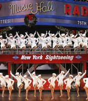 "In ""New York at Christmas,"" the Rockettes board a real double-decker Gray Line tour bus and whiz past a kinetic montage of New York landmarks, including the Empire State Building and Statue of Liberty."