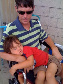 Shane FitzMaurice, terminally ill with ALS, holds his youngest son on his lap.