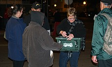 A volunteer hands out gloves outside the winter homeless shelter on December 4, 2009. Many homeless people know exactly where and what time certain organizations bring supplies downtown and they intentionally arrange their schedules to meet these volunteers.