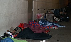 Homeless people bunker down for the night as early as 7 p.m. across the street from the winter homeless shelter.